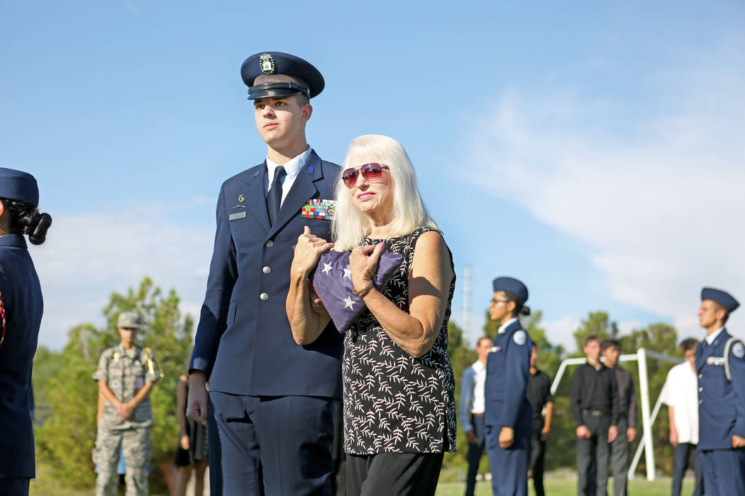 Air Force JROTC'S vice missions support group commander Darren Cull, 17, left, walks down Gail Fahy, previous Palo Verde high school's foreign language chair and best friend of the school's foreig ...