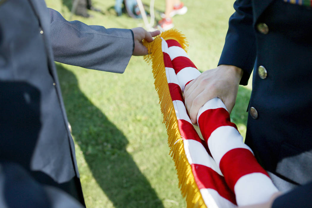 The Color Guard finishes rolling a flag after Palo Verde High School's Air Force JROTC's annual rededication ceremony in remembrance of the victims, including the school's foreign languages teache ...