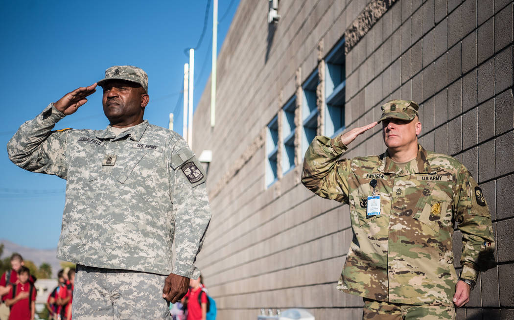 Sgt. Major Gary Schoolfield, left, and MSG Michael Kutsen, right, salute the Cheyenne High School Color Guard at Joseph M. Neal STEAM Academy on Monday, Sep. 11, 2017, in Las Vegas. Morgan Lieberm ...