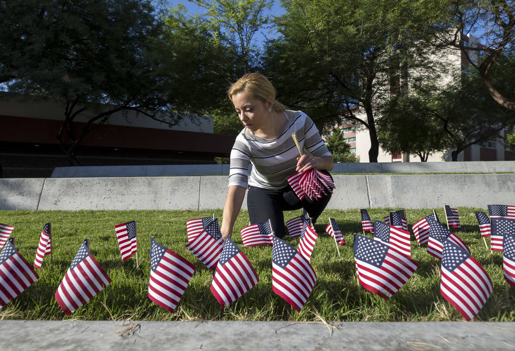 UNLV sophomore Nicole Mirkovic places one of the 3,000 flags ahead of a ceremony in remembrance of the Sept. 11 terrorist attacks on Monday morning, Sept. 11, 2017, outside the student union build ...