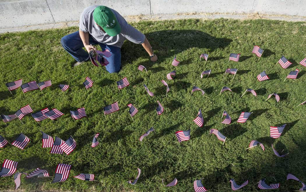 Mike Radza places one of the 3,000 flags ahead of a ceremony in remembrance of the Sept. 11 terrorist attacks on Monday morning, Sept. 11, 2017, outside the student union building at UNLV in Las V ...