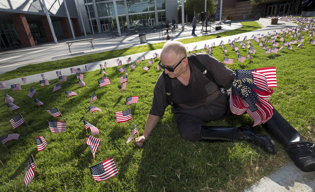 Retired New York City police officer and UNLV alumnus Seth Kimmel helps place one of the 3,000 flags ahead of a ceremony in remembrance of the Sept. 11 terrorist attacks on Monday morning, Sept. 1 ...