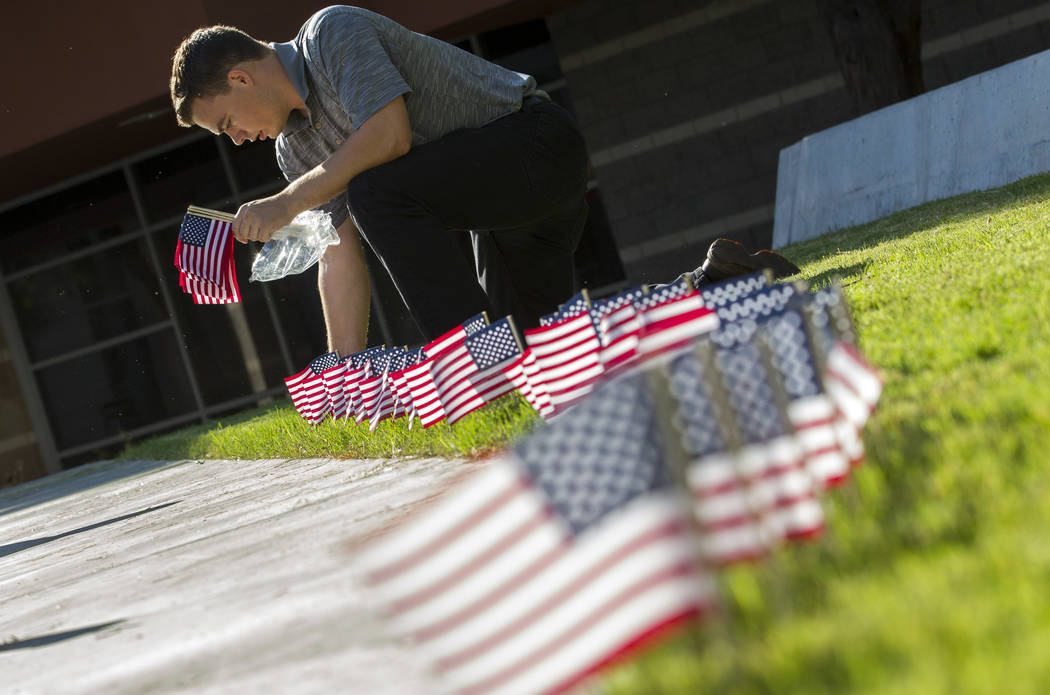 Jacob Deaville, president of the UNLV College Republicans, places one of the 3,000 flags ahead of a ceremony in remembrance of the Sept. 11 terrorist attacks on Monday morning, Sept. 11, 2017, out ...