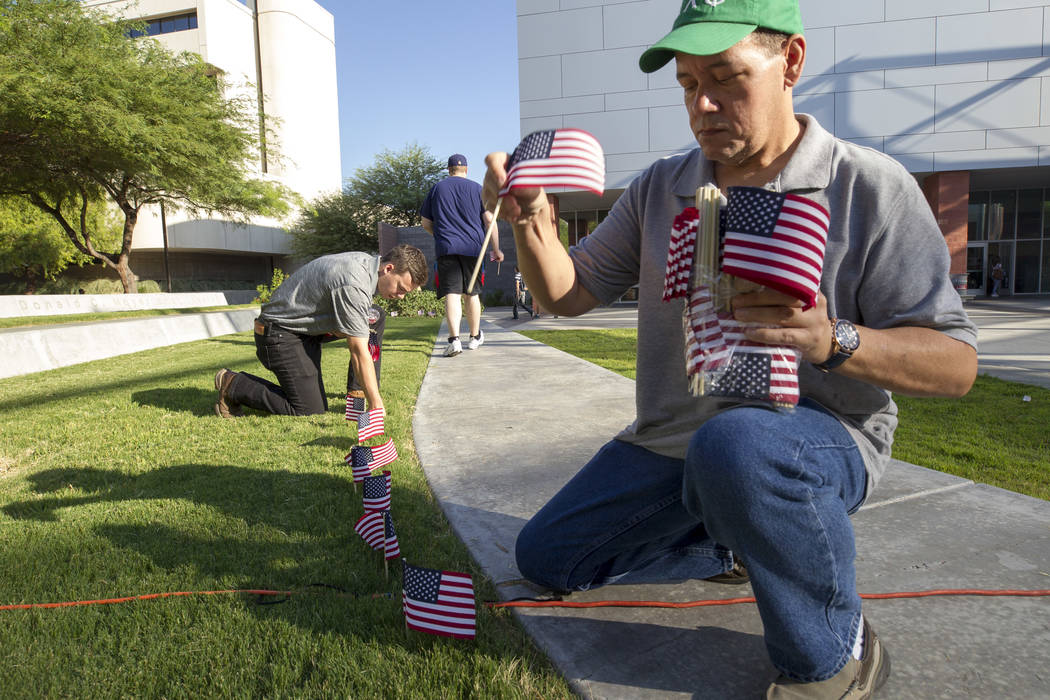 Mike Radza, right, and Jacob Deaville place flags in the grass ahead of a ceremony in remembrance of the Sept. 11 terrorist attacks on Monday morning, Sept. 11, 2017, outside the student union bui ...