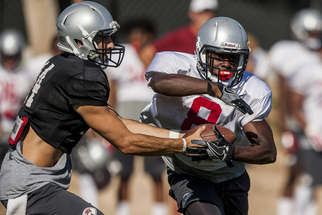 UNLV running back Charles Williams receives a handoff from quarterback Kurt Palandech during training camp at Rebel Park on Tuesday, Aug. 8, 2017.  Patrick Connolly Las Vegas Review-Journal @PConnPie