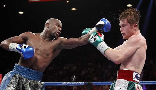 Floyd Mayweather hits Canelo Alvarez during their WBC and WBA super welterweight title bout at the MGM Grand in Las Vegas Saturday, Sept. 14, 2013. (John Locher/Las Vegas Review-Journal)