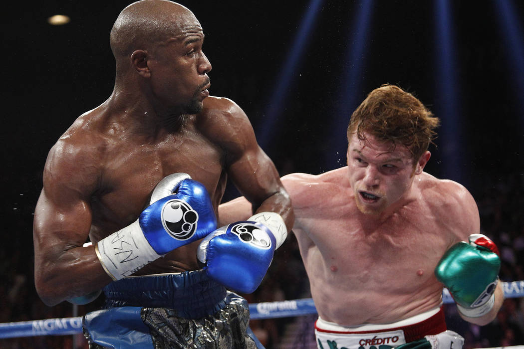 Canelo Alvarez, left, takes a swing at Floyd Mayweather during their WBC and WBA super welterweight title bout at the MGM Grand in Las Vegas Saturday, Sept. 14, 2013. Las Vegas Review-Journal File ...