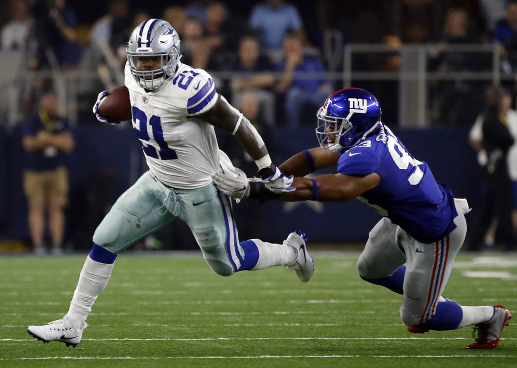 Dallas Cowboys running back Ezekiel Elliott (21) escapes a tackle attempt by New York Giants linebacker B.J. Goodson (93) in the second half of an NFL football game, Sunday, Sept. 10, 2017, in Arl ...