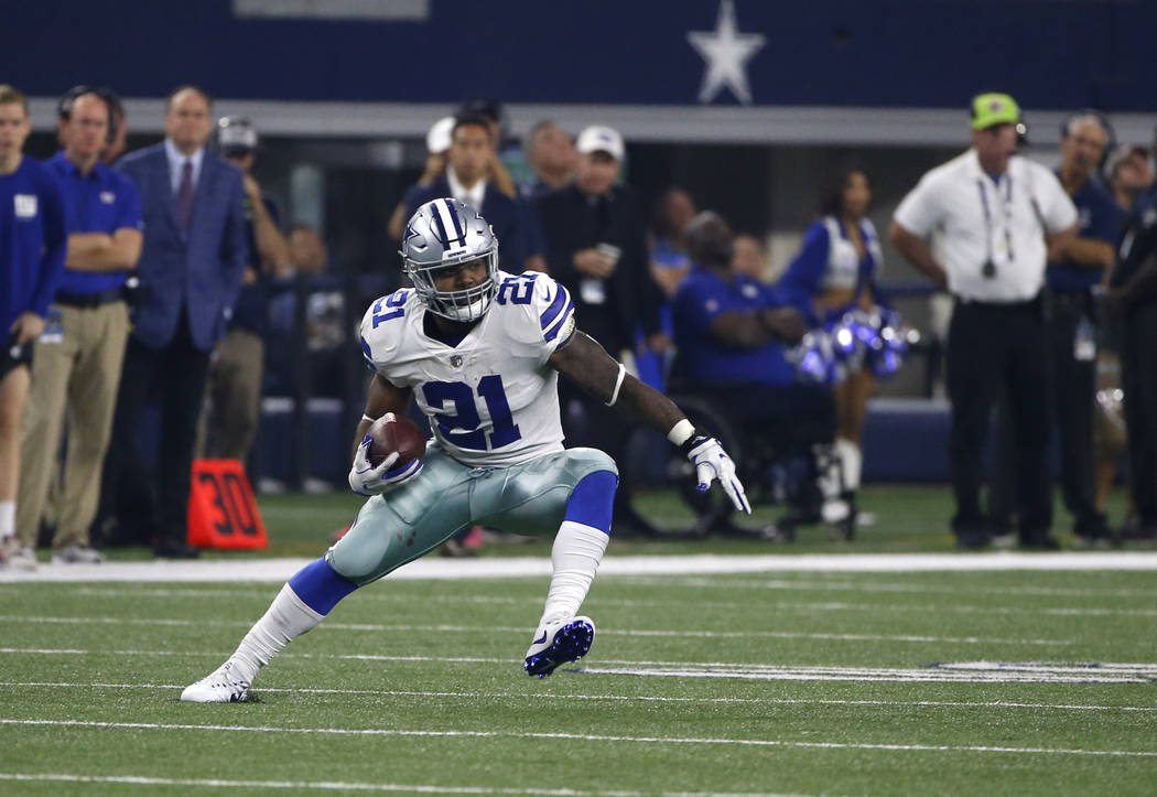 Dallas Cowboys running back Ezekiel Elliott (21) carries the ball for extra yardage against the New York Giants in the second half of an NFL football game, Sunday, Sept. 10, 2017, in Arlington, Te ...