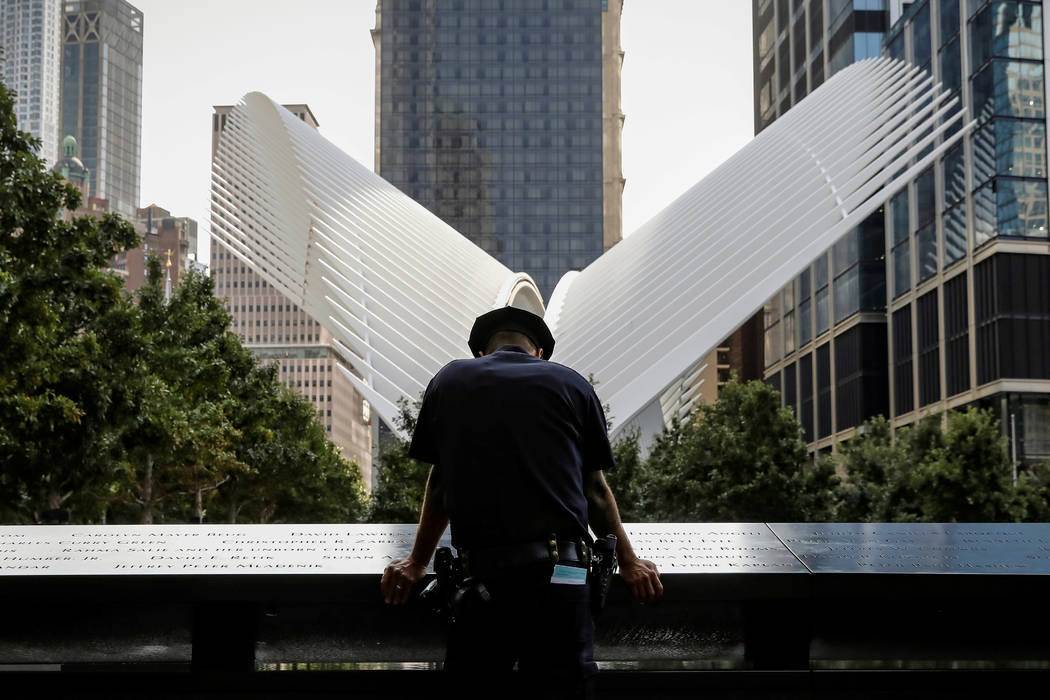 A New York City Police Department officer pauses at the edge of the reflecting pool at the National 9/11 Memorial and Museum during ceremonies marking the 16th anniversary of the attacks in New Yo ...