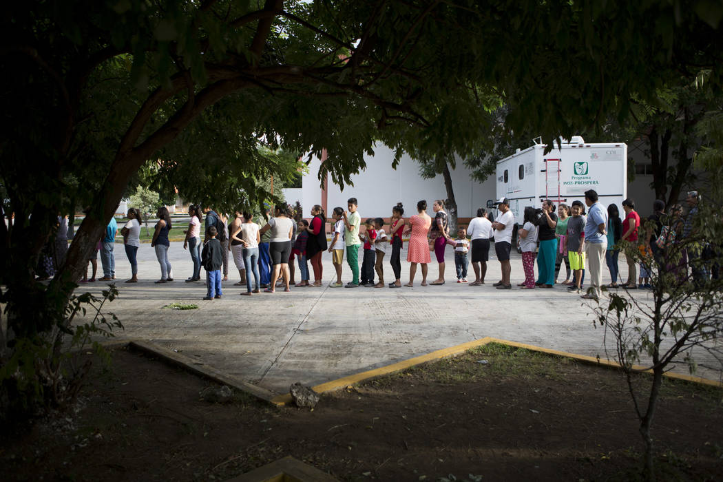 People taking shelter at a technology school after their homes were destroyed or damaged in Thursday's magnitude 8.1 earthquake, wait in line to receive breakfast in Juchitan, Oaxaca state, Mexico ...