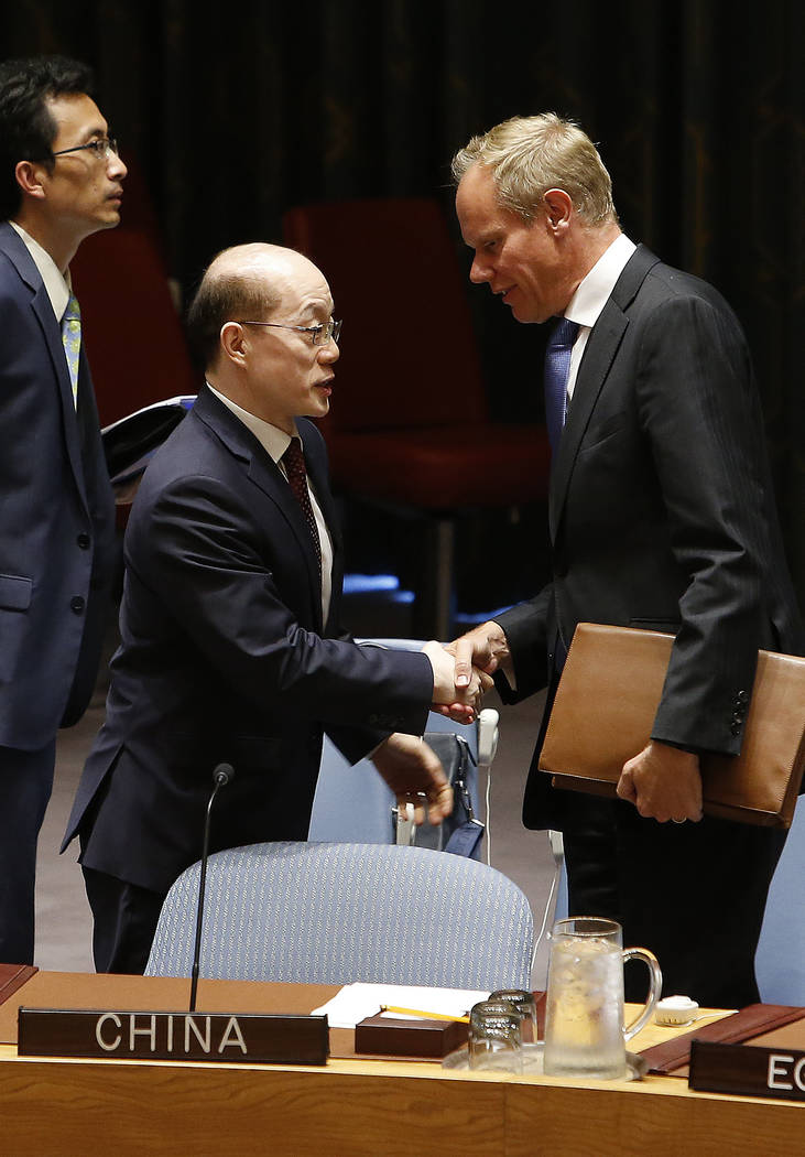 China's United Nations Ambassador Liu Jieyi, left, speaks to the United Kingdom's U.N. Ambassador Matthew Rycroft before a vote to adopt a new sanctions resolution against North Korea during a mee ...