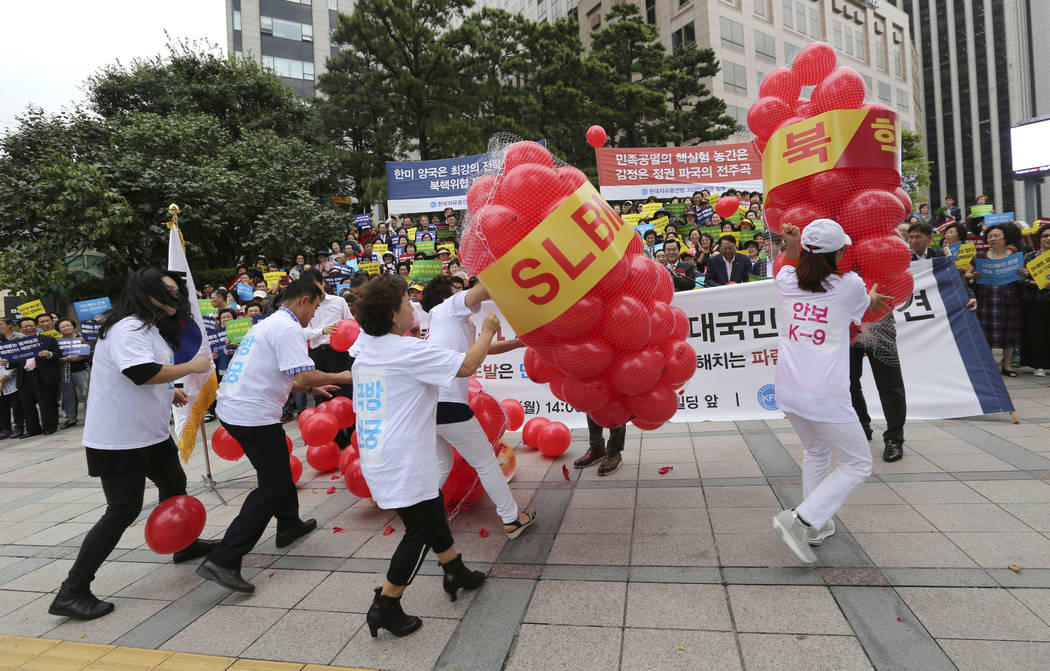 Members of Korea Freedom Federation beat balloons symbolizing North Korean weapons during a rally to denounce North Korea's nuclear test in Seoul, South Korea, Monday, Sept. 11, 2017. North Korea  ...