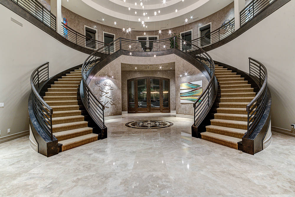 The home's dramatic staircase is under a Bocci chandelier. (The Napoli Group)