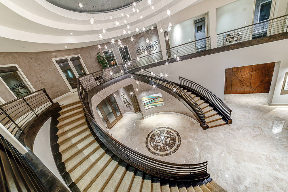 Two dramatic staircases link the upper and lower levels of the home. (The Napoli Group)