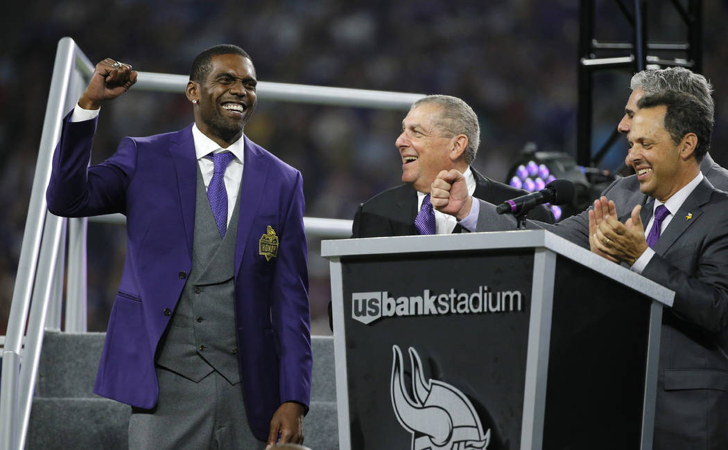 Former Minnesota Vikings wide receiver Randy Moss, left, reacts as he is inducted into the Vikings Ring of Honor during halftime of an NFL football game between the Vikings and the New Orleans Sai ...