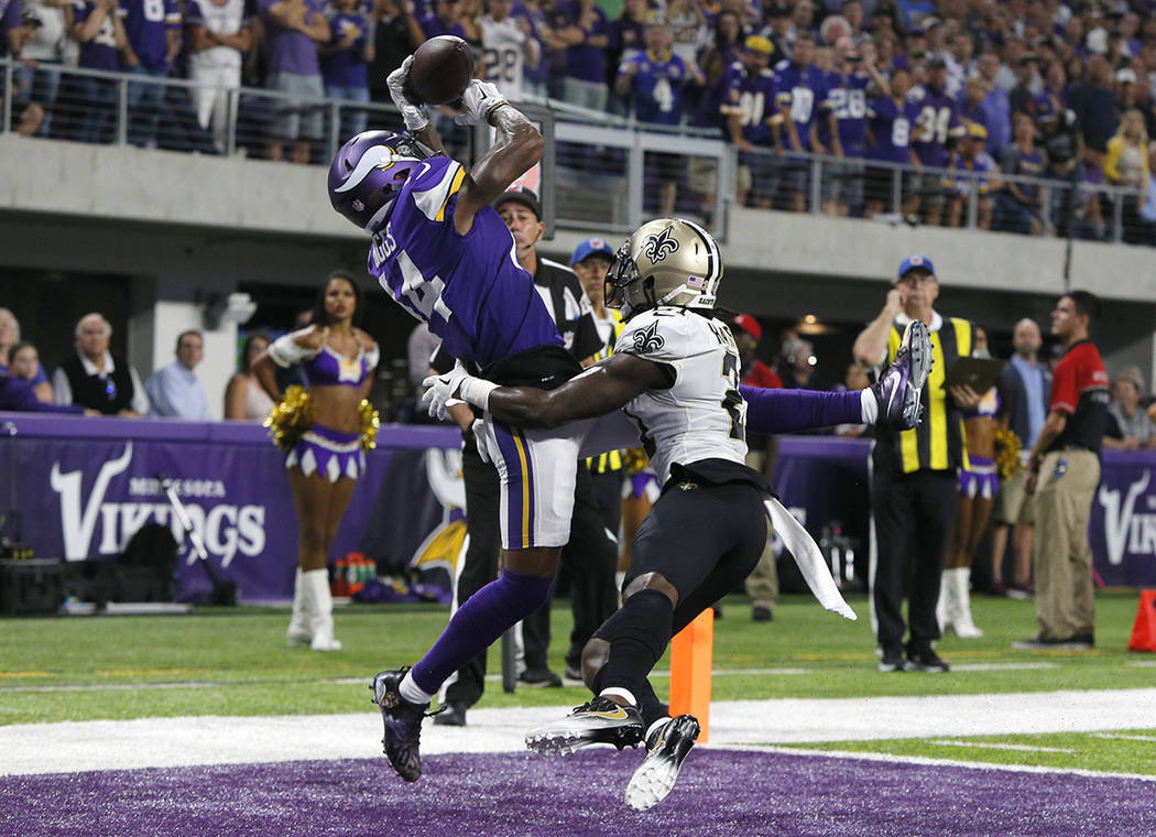 Minnesota Vikings wide receiver Stefon Diggs, left, catches a 2-yard touchdown pass over New Orleans Saints cornerback De'Vante Harris during the first half of an NFL football game, Monday, Sept.  ...