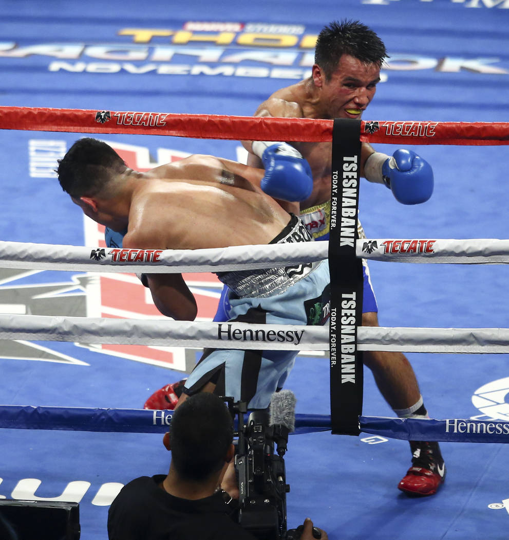 Joseph Diaz Jr., left, takes a hit from Rafael Rivera during their WBC featherweight title eliminator boxing match at T-Mobile Arena in Las Vegas on Saturday, Sept. 16, 2017. Chase Stevens Las Veg ...