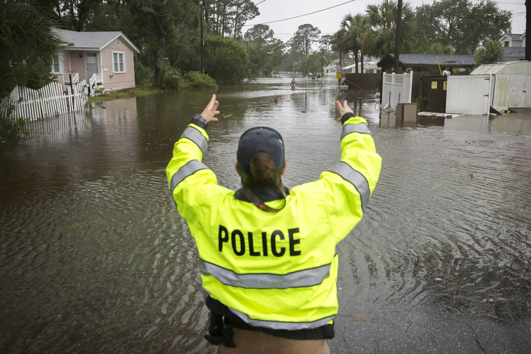 A City of Tybee police officer checks the well being of a resident fleeing her flooded home on Tybee Island, Ga., Monday, Sept., 11, 2017. Parts of the coastal Georgia island suffered from Tropica ...