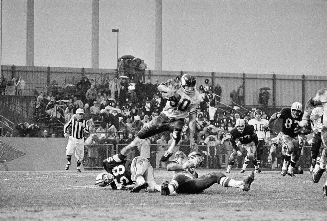 Viking fullback Billy Brown (30) hurtles over Green Bay linebacker Dan Currie (58) and teammate Milt Sunde (64) in Minneapolis, on Nov. 1, 1964. He wasn?t in the clear however as he was brought do ...