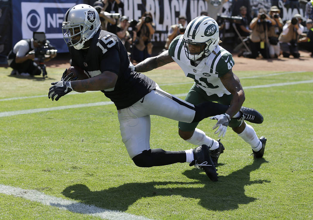 Oakland Raiders wide receiver Michael Crabtree (15) catches a touchdown pass against New York Jets defensive back Buster Skrine (41) during the first half of an NFL football game in Oakland, Calif ...