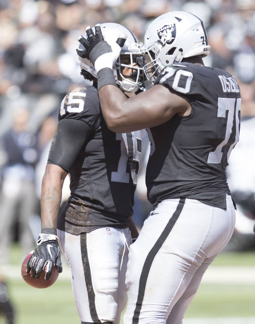 Oakland Raiders offensive guard Kelechi Osemele (70) celebrates with wide receiver Michael Crabtree (15) after a catch in the first half of their game against the New York Jets in Oakland, Calif., ...