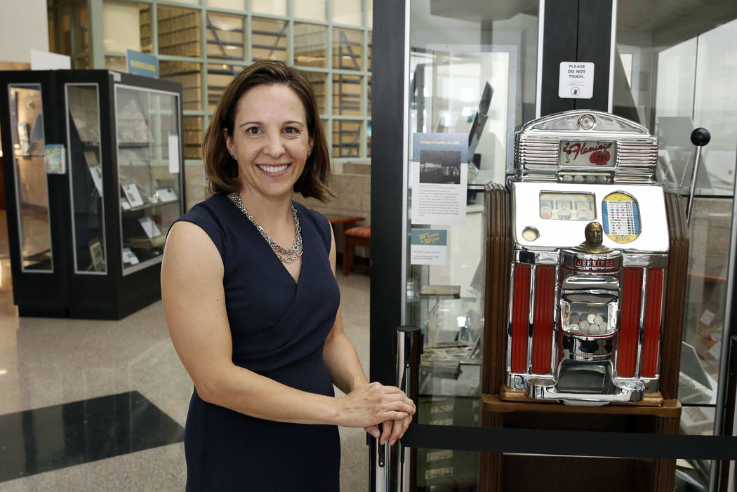 Michelle Light, director of special collections and archives at the UNLV University Libraries, poses for photo next to Flamingo slot machine, circa 1950 at Lied Library on Friday, Sept. 15, 2017,  ...