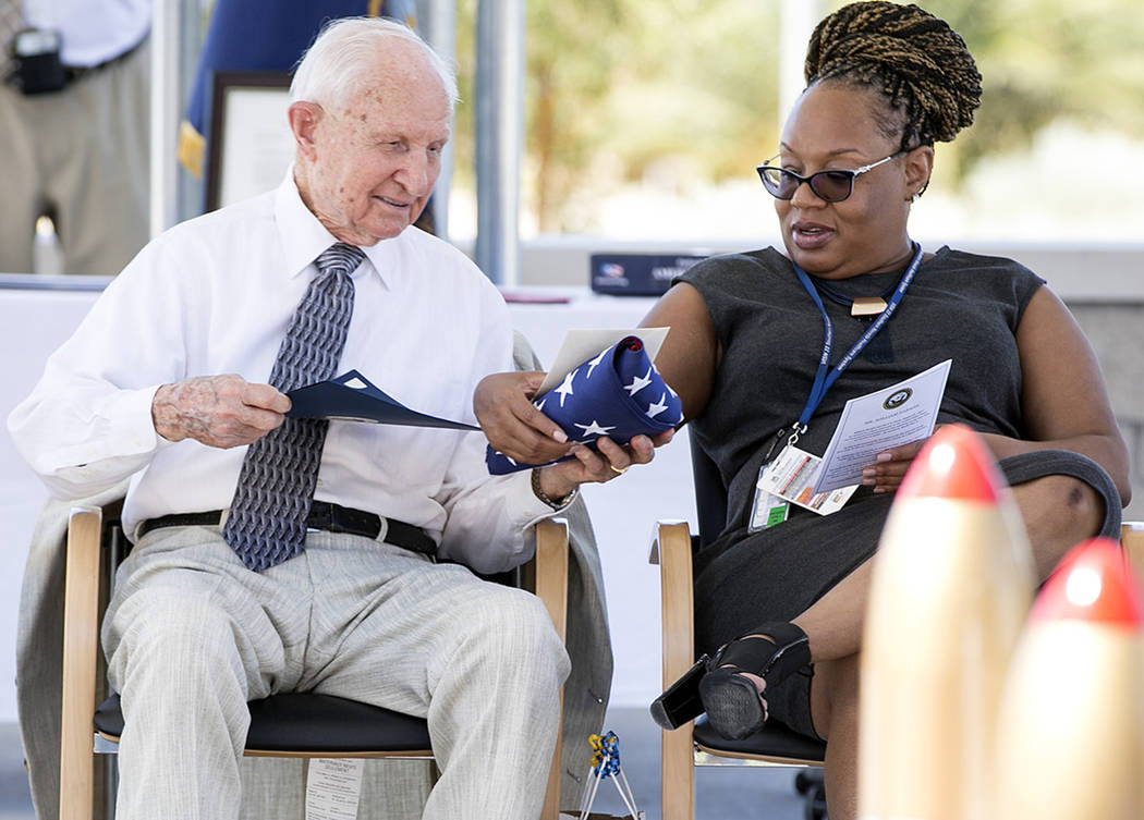 World War II Navy veteran William Darwin, left, shows a flag honored to him and other letters and certificates for his 100th birthday to medical support Tanika Copeland at the VA Medical Center on ...