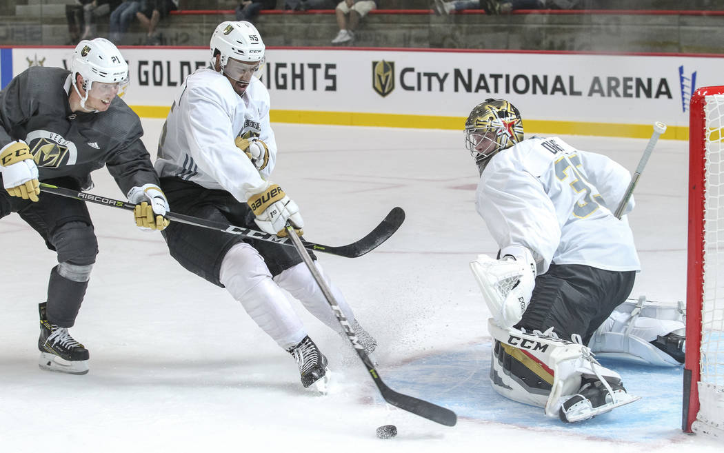 Vegas Golden Knights' Keegan Kolesar, center, is pressured by Cody Eakin, left, as he takes a shot on goalie Oscar Lindberg in a scrimmage game during team practice at the City National Arena on F ...