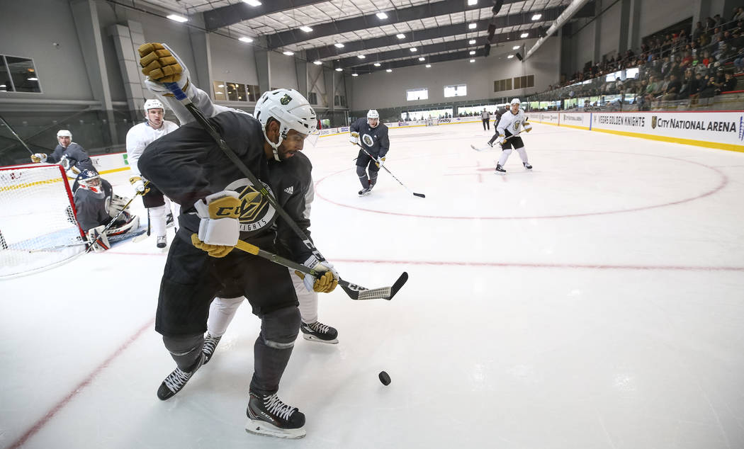 Vegas Golden Knights left defenseman Brad Hunt, foreground, (77) is pressured by Golden Knights left wing Pierre-Edouard Bellemare (41) as they vie for the puck in a scrimmage game during the NHL  ...