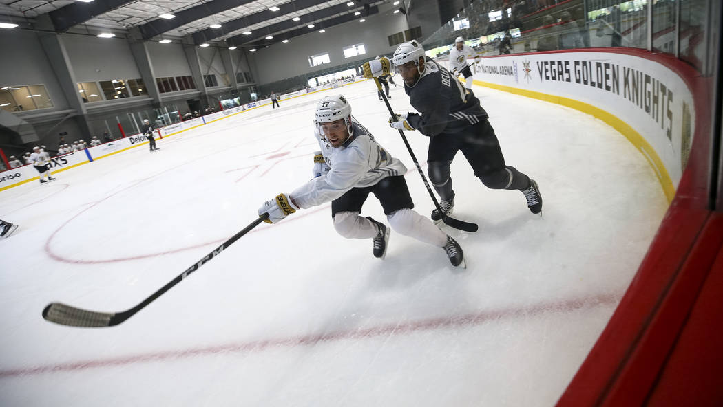 Vegas Golden Knights left defenseman Brad Hunt, left, (77) and Golden Knights left wing Pierre-Edouard Bellemare (41) chase the puck in a scrimmage game during the NHL team's practice at the City  ...