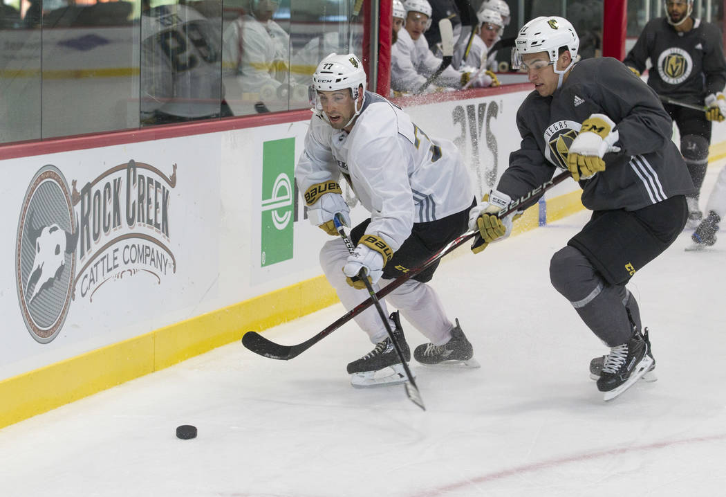 Vegas Golden Knights left defenseman Brad Hunt, left, (77) and Golden Knights forward Nick Suzuki (17) chase the puck in a scrimmage game during the NHL team's practice at the City National Arena  ...