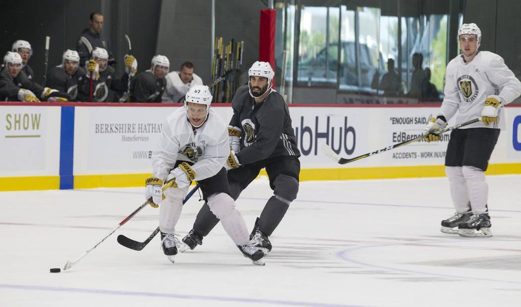 Vegas Golden Knights left wing Temmu Pulkkinen, left, (67)  reaches for the puck as Golden Knights left defenseman Jason Garrison (7) trails behind in a scrimmage game during the NHL team's practi ...