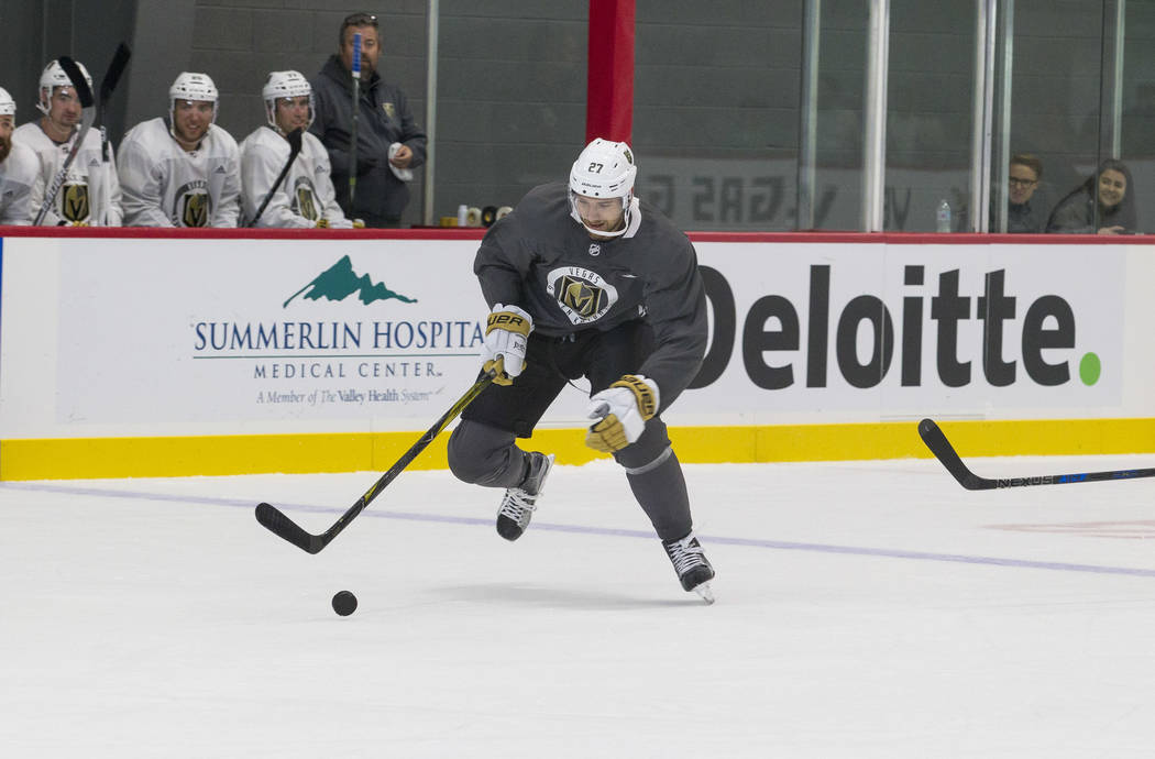Vegas Golden Knights left defenseman Shea Theodore (27) attempts to gain control of the puck in a scrimmage game during the NHL team's practice at the City National Arena in Las Vegas, Saturday, S ...