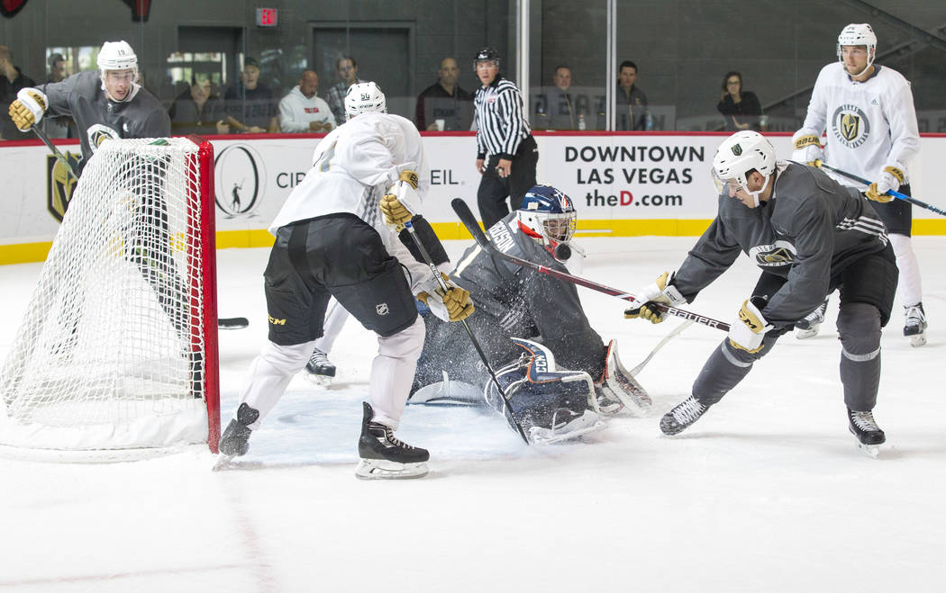Vegas Golden Knights goaltender Dylan Ferguson, center,  (1) blocks a shot from Golden Knights forward Nick Suzuki, second right, (17) in a scrimmage game during the NHL team's practice at the Cit ...