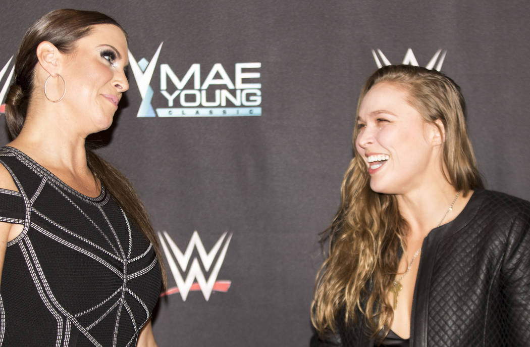 Former UFC women's bantamweight champion Ronda Rousey, right, shares a moment with WWE Chief Brand Officer Stephanie McMahon at the WWE Mae Young Classic event at the Thomas & Mack Center in L ...