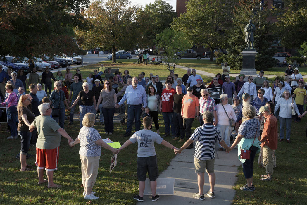 """A chorus of """"We Shall Overcome"""" rises from a gathering against racism in Broad Street Park in Claremont, N.H., Tuesday, Sept. 12, 2017. The demonstration was inspired by violence ..."""