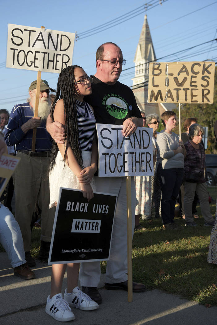 Katrina Roberge, 14, of Lebanon, N.H., stands with her father John Roberge in silence during a gathering at Broad Street Park in Claremont, N.H., Tuesday, Sept. 12, 2017, to show support for an 8- ...