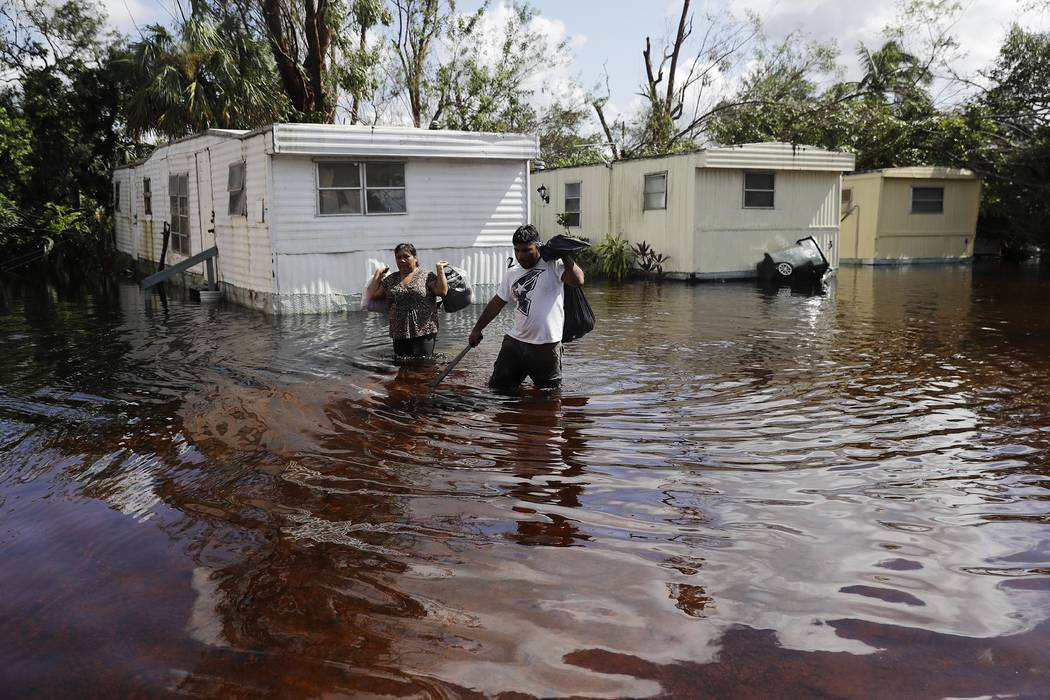 Angelina Ventura, left, and Jose Gonzalez retrieve belongings from their flooded home in the wake of Hurricane Irma in Bonita Springs, Fla., Tuesday, Sept. 12, 2017. (AP Photo/David Goldman)