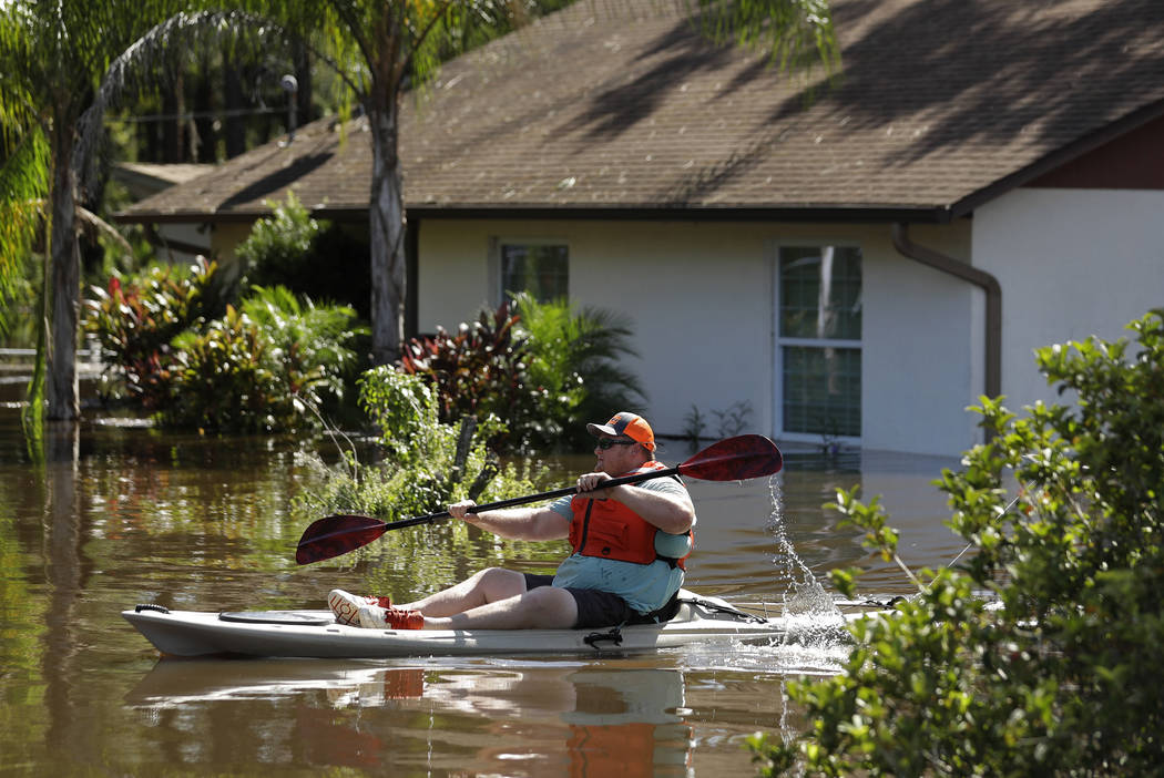 A man paddles a kayak near a flooded home along the Alafia River Tuesday, Sept. 12, 2017, in Lithia, Fla. A storm surge from Hurricane Irma pushed water into the low lying area. (AP Photo/Chris O' ...