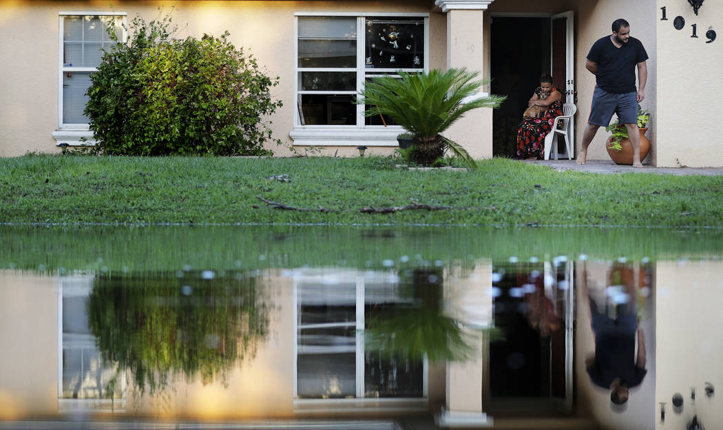 Sandra Pagan, left, escapes the heat inside her home with her dog Goldo and nephew Misael Fernandez after Hurricane Irma flooded their neighborhood leaving them without power and impassable with t ...