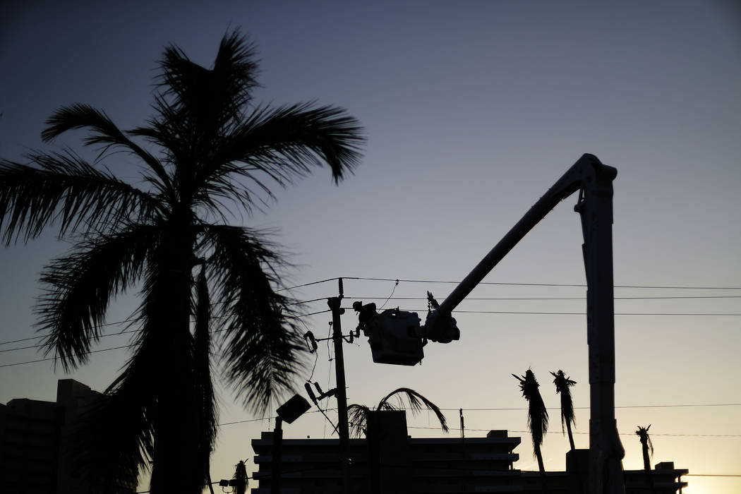 A worker is silhouetted against the setting sun as he works on a power line in the aftermath of Hurricane Irma in Marco Island, Fla., Tuesday, Sept. 12, 2017. Florida officials say crews are resto ...