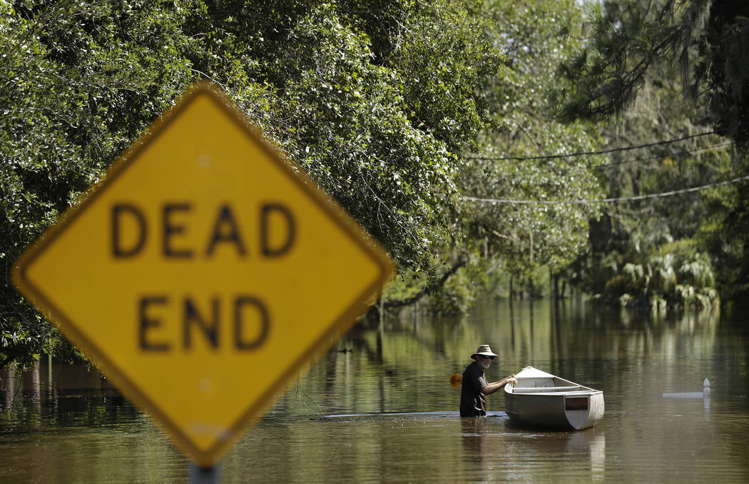 A man, who refused to be identified, pushes a canoe through water from the Alafia River Tuesday, Sept. 12, 2017, in Lithia, Fla. A storm surge from Hurricane Irma pushed water into the low lying a ...