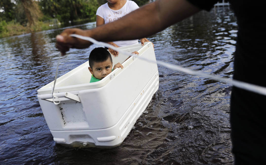 Alfonso Jose Jr., 2, is floated down his flooded street by his parents as the wade through water to reach an open convenience store in the wake of Hurricane Irma in Bonita Springs, Fla., Tuesday,  ...