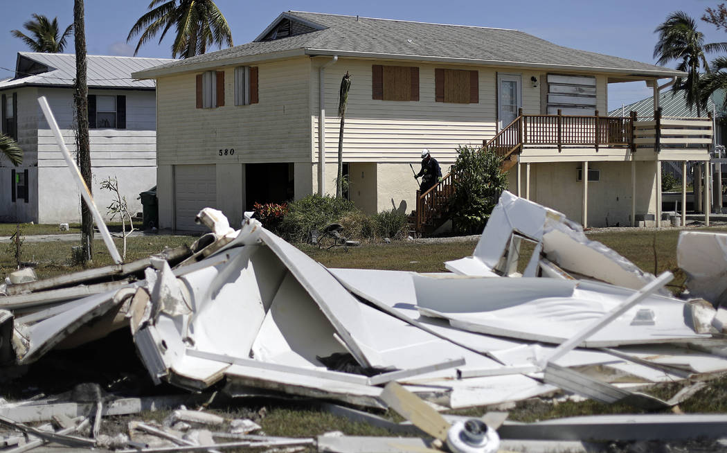 A member of the Arizona Task Force 1 search and rescue team knocks on doors while checking on homes and their owners after Hurricane Irma in Goodland, Fla., Tuesday, Sept. 12, 2017. (AP Photo/Davi ...