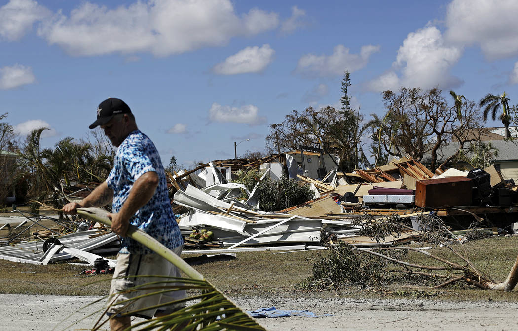 Rob Brehm cleans up debris from his home as a demolished house sits across the street after Hurricane Irma in Goodland, Fla., Tuesday, Sept. 12, 2017. (AP Photo/David Goldman)