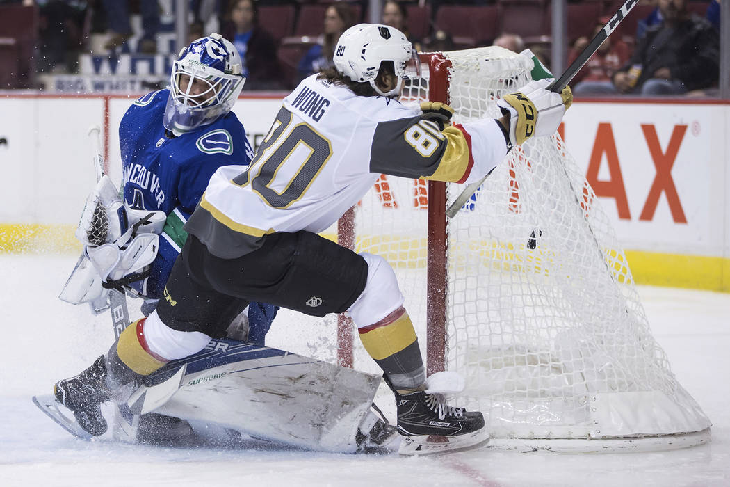 Vegas Golden Knights' Tyler Wong (80) scores his first goal against Vancouver Canucks' goalie Richard Bachman during the first period of a preseason NHL hockey game in Vancouver, British Columbia, ...