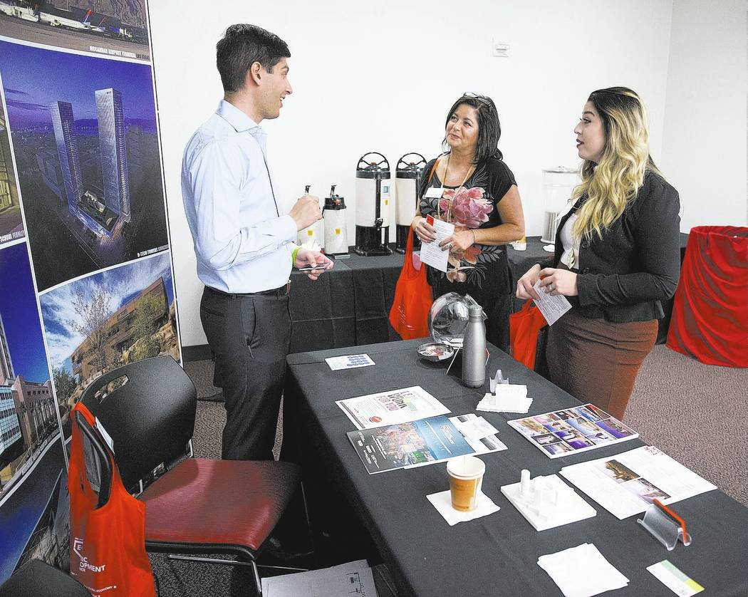 Exhibitor Chris Lujan, from left, senior associate for TSK Architects, speaks with Deborah Stewart and Sara Champneys of the Churchill Economic Development Authority, during the Nevada Economic De ...