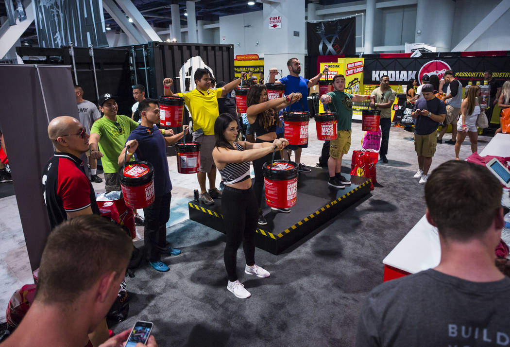 Attendees lift buckets of Carnivor Mass supplements during Joe Weider's Olympia's Fitness & Performance Expo at the Las Vegas Convention Center in Las Vegas on Friday, Sept. 15, 2017. Chase St ...