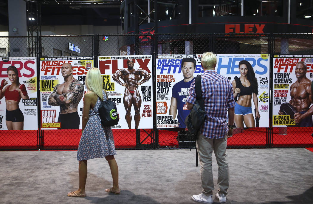 Attendees walk by a display of magazines during Joe Weider's Olympia's Fitness & Performance Expo at the Las Vegas Convention Center in Las Vegas on Friday, Sept. 15, 2017. Chase Stevens Las V ...